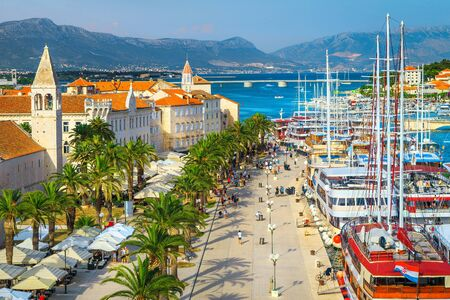 Popular travel and touristic location. Picturesque view from the Kamerlengo castle. Promenade with palm trees, cozy street cafes and restaurants. Medieval old town with anchored boats and luxury yachts, Trogir, Dalmatia, Croatia, Europe Stock Photo