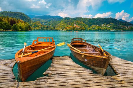 Cute wooden rowing boats anchored at the pier on the lake Bled. Famous Pillgrimage church and small island in background, Bled, Slovenia, Europe