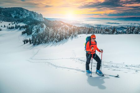 Cheerful backpacker woman on fresh powder snow, ski touring on the snowy slopes. Backcountry skier woman with colorful backpack and mountain equipment on the hill, Carpathians, Transylvania, Romania, Europe Фото со стока