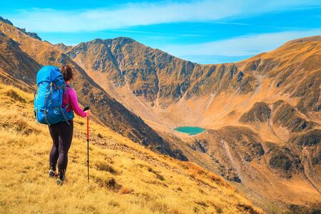Traveller active hiker woman with colorful backpack enjoying the view from the hills, Fagaras mountains, hiking and travel concept, Carpathians, Romania, Europe Фото со стока