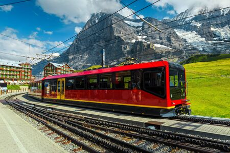 Famous Swiss excursion destination. Spectacular travel and touristic place with high mountains and stunning view. Modern electric red tourist train in Kleine Scheidegg station, Grindelwald, Bernese Oberland, Switzerland, Europe