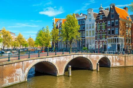 Picturesque travel and touristic location. Beautiful water canals and waterways with spectacular traditonal dutch buildings, Amsterdam, Netherlands, Europe