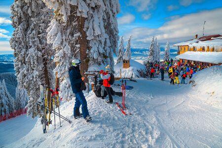 Gruppe sportlicher Skifahrer, die sich entspannen und die Aussicht genießen. Skifahrer entspannen auf der Terrasse des Bergrestaurants und Café Chalet, Skigebiet Poiana Brasov, Karpaten, Siebenbürgen, Rumänien, Europe