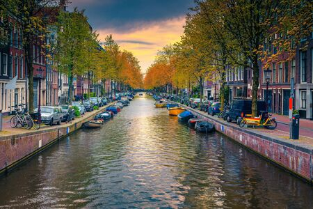 Stunning travel destination, narrow waterway and waterfront with traditional dutch houses. Colorful boats moored in water canal at sunset, Amsterdam, Netherlands, Europe