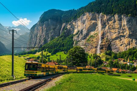 Unforgettable travel experience, modern electric tourist train and Lauterbrunnen village with high waterfalls in background, near Wengen village, Bernese Oberland, Switzerland, Europe 스톡 콘텐츠