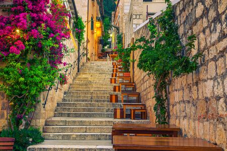 Cozy narrow street with street cafe and restaurant at morning. Rustic street with stone houses and colorful bougainvillea mediterranean flowers, Hvar town, Hvar island, Dalmatia, Croatia, Europe