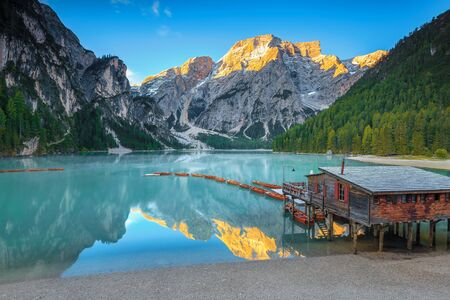 Breathtaking alpine touristic, recreation, hiking and photography place. Cute wooden boathouse and wooden boats in row on the lake, Lake Braies, Dolomites, Italy, Europe