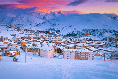 Beautiful winter sport and travel destination. Well known winter ski resort and stunning ski slopes at colorful sunset, Alpe d Huez, France, Europe Stockfoto