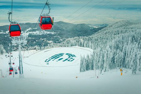Admirable snow covered trees and winter ski resort with colorful fast cable cars. Ski slope and frozen lake in Poiana Brasov famous ski resort, Transylvania, Romania, Europe 免版税图像