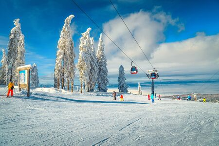 Spectacular snow covered trees and winter ski resort with colorful fast ski lifts. Skiers downhill on the ski slopes in Poiana Brasov ski resort, Transylvania, Romania, Europe