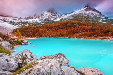 Snowy misty mountains at colorful sunset. Popular touristic and hiking destination with famous Sorapis turquoise lake, Dolomites, Italy, Europe