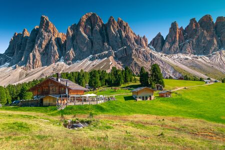 Picturesque spring alpine landscape, touristic mountain chalets and small lake with high snowy mountains in background, Geisler - Odle mountain group, Alto Adige, Dolomites, Italy, Europe