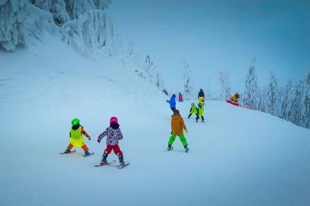 Majestic snow covered trees and winter ski resort. Active kids skiers skiing downhill in popular Poiana Brasov ski resort, Transylvania, Romania, Europe Stock Photo