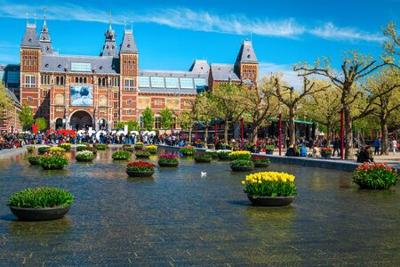 AMSTERDAM, NETHERLANDS - APRIL 30, 2017: National State Museum (Rijksmuseum) building, small pond decorated with colorful flowers and IAMSTERDAM words sign, Netherlands, Europe APRIL 30, 2017 in Amsterdam, Netherlands Editorial