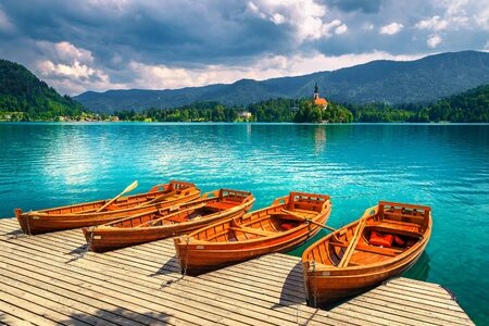 Old wooden rowing boats moored at the pier on the lake Bled. Gorgeous Pillgrimage church and small island in background, Bled, Slovenia, Europe