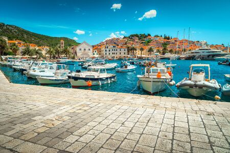 Popular medieval mediterranean resort with beautiful harbor and majestic cityscape. Luxury yachts, sailing boats and fishing boats anchored in Hvar town harbor, Hvar island, Dalmatia, Croatia, Europe