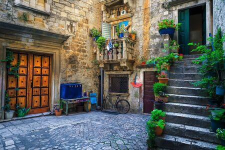 Piękna wąska uliczka z kamiennymi domami. Stare kamienne domy i wejścia ozdobione kwiatami. Przytulne apartamenty i brukowana ulica z kwiecistymi wejściami, Trogir, Dalmacja, Chorwacja, Europa