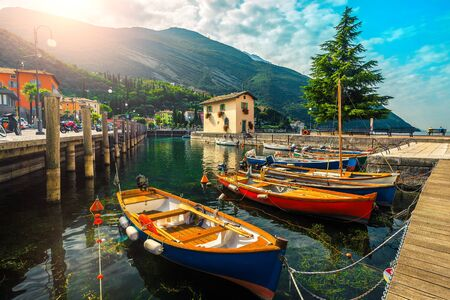 Spectacular waterfront and harbor with anchored colorful wooden boats on the lake Garda, Torbole resort, Italy, Europe 免版税图像