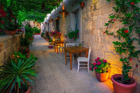 Cozy narrow street with ambiance street cafe and restaurant at morning. Flowery entrance and street lights, Hvar town, Hvar island, Dalmatia, Croatia, Europe