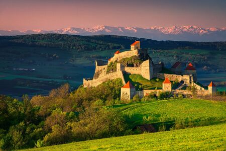 Majestic Rupea fortress on the hill, beautiful fortification and high snowy mountains in background, Brasov, Transylvania, Romania, Europe