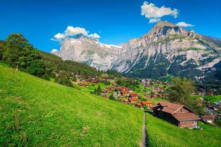 Fantastic summer mountain resort with alpine wooden houses and high snowy mountains in background, Grindelwald, Bernese Oberland, Switzerland, Europe