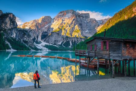 Backpacker tourist enjoying the view on the shore of lake Braies. Picturesque place with snowy mountains and wooden boats on the lake, Dolomites, Italy, Europe Standard-Bild