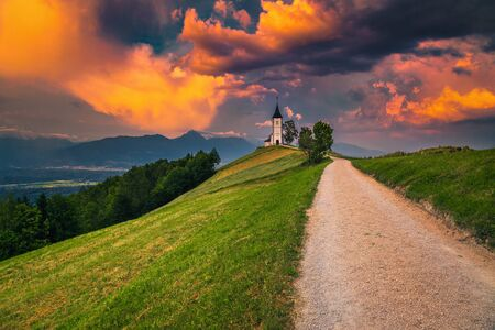 Magical sunset landscape with cute church on the hill. Alpine landscape and gorgeous charming Saint Primoz church with mountains in background at sunset, Jamnik village, Slovenia, Europe Фото со стока