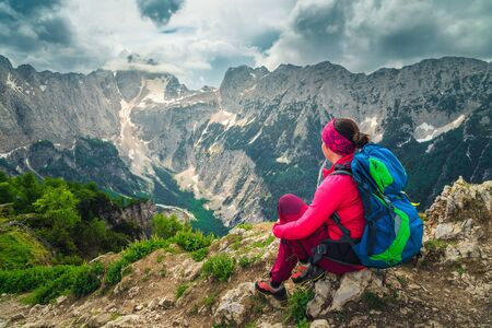 Cheerful hiker woman with colorful backpack. Freedom hiker woman sitting and enjoying the view with Jalovec mountain peak, from the Slemenova Spica hiking place, Julian Alps, Slovenia, Europe