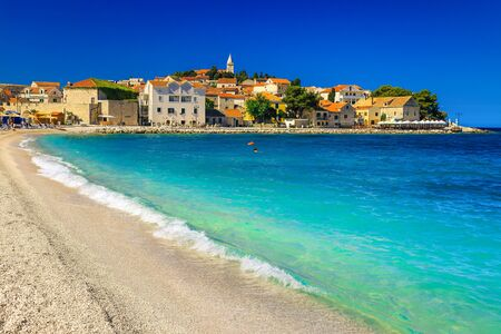 Picturesque sandy beach resort with waves and old mediterranean buildings in background, Primosten, Dalmatia, Croatia, Europe