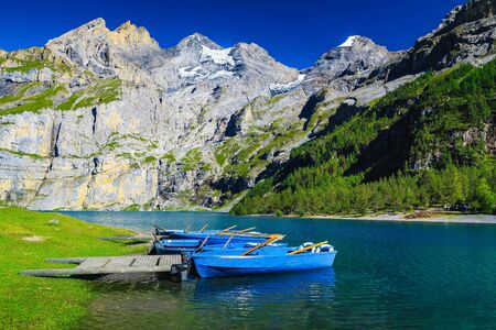 Popular hiking and leisure place with lake Oeschinensee. Moored recreation boats and high mountains with glaciers in background, Bernese Oberland, Switzerland, Europe