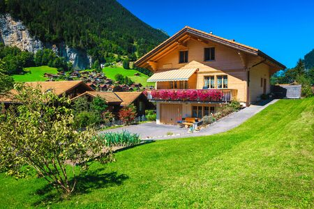 Cute wooden house with flowery terrace and small vegetable garden, Switzerland, Europe
