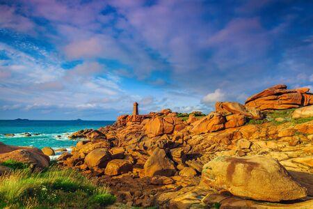 Cute lighthouse on the rocky Atlantic ocean coast in Ploumanach, Perros Guirec, Brittany, France, Europe