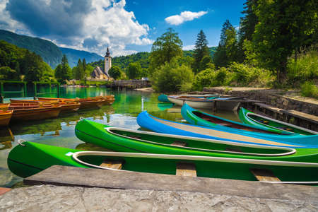 Colorful canoes, kayaks and wooden rowing boats on the lake. Recreation and sport objects on the lake Bohinj, Ribcev Laz, Slovenia, Europe