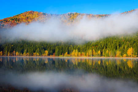 Misty autumn landscape with colorful deciduous trees in the forest and famous volcanic lake. Popular touristic and travel place with Saint Ana lake, Transylvania, Romania, Europe