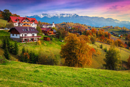 Popular rural touristic places with spectacular gardens and high snowy mountains in background. Autumn landscape with deciduous trees and houses on the hill, Magura, Transylvania, Romania, Europe Foto de archivo