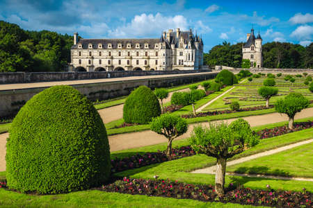 Amazing orderly ornamental garden with walkways and picturesque Chenonceau castle in background, Loire valley, France, Europe 免版税图像