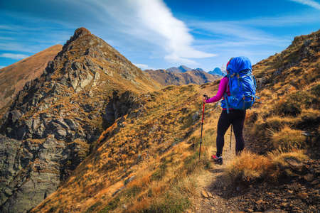 Cheerful hiker woman with backpack enjoying the view on the hiking trail, Fagaras mountains, hiking and travel concept, Carpathians, Romania, Europe Stockfoto