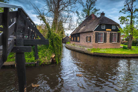 Traditional thatched roof house on the green small island and wooden bridge over the water canal, Giethoorn, Netherlands, Europe