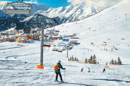 Easy ski slopes with exercising skiers. French ski resort with ski lifts, cable cars and wooden buildings in background, Alpe d Huez, France, Europe Reklamní fotografie