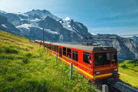Mountain railroad with modern cogwheel red tourist train on the slope. One of the most famous railway, Jungfraujoch, Kleine Scheidegg, Grindelwald, Bernese Oberland, Switzerland, Europe
