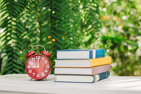Education concept, Book and Clock with green blur background.,Books stacking. Stock Photo