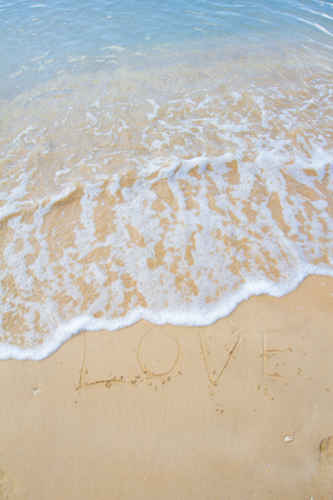 valentine s day beach: The inscription on the sand near the sea and the waves - I love you. Background.