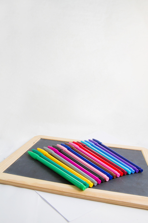Colorful markers pens on black board for text