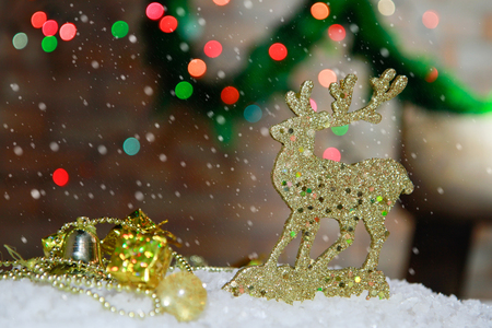 Happy New Year decoration gold deer toy  Christmas ornaments arranged into a holiday festive scene  with bokeh light and chrismas tree  background