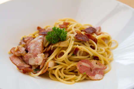 spaghetti spicy with bacon, parsley and parmesan cheese Fresh pepper, Basil leaf . Pasta Carbonara on white plate. Italian food concept.