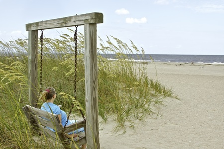 tybee island: Woman sitting by the ocean thinking and relaxing
