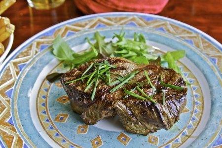 A thick cut juicy steak on a colorful plate Stok Fotoğraf