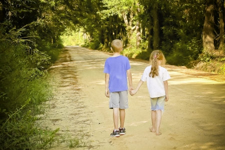 Boy and girl on a dirt road holding hands photo