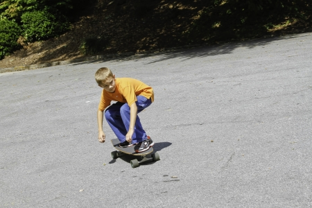 Young male skatboarding down a hill Stok Fotoğraf