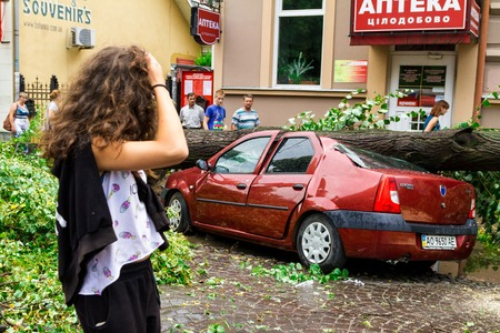 Uzhgorod, Ukraine - July 26. 2016:  The locals pass near the car, crushed by a tree felled by hurricane. Editorial
